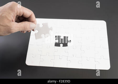 Hand placing last piece into jigsaw puzzle, Bavaria, Germany