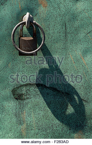 Close-up of a metal ring/handle and padlock casting a shadow on green metal - Stock Photo