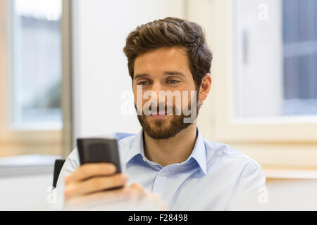 Cheerful bearded man using his smartphone in modern office - Stock Photo