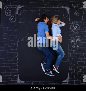 Young couple sleeping in bed, holding hands, the man is embracing his woman. Young dad sleeping with a hand on mom's - Stock Photo