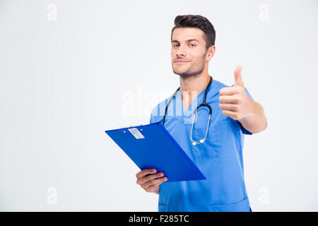 Portrait of a handsome male doctor holding clipboard and showing thumb up isolated on a white background - Stock Photo