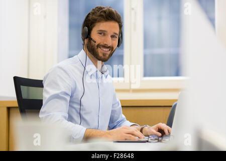 smiling man wearing headset using laptop - Stock Photo