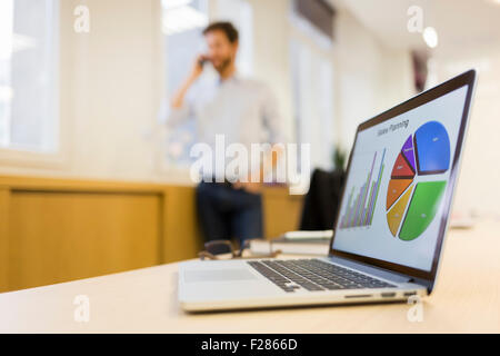 Businessman talking on cell phone in office - Stock Photo