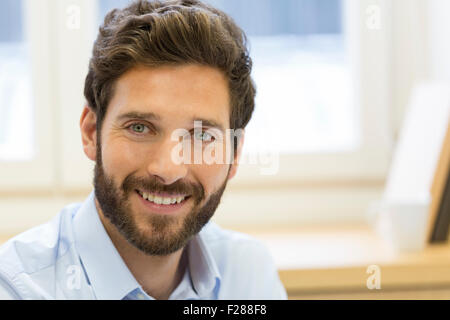 Portrait of handsome bearded man in office. looking camera - Stock Photo