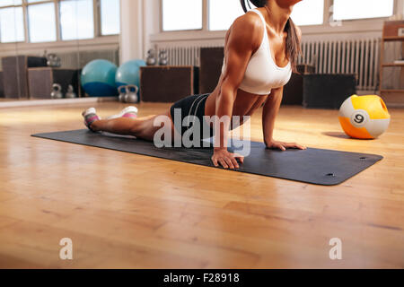 Cropped shot of young woman stretching her stomach on fitness mat. Muscular female doing stretching exercise in - Stock Photo