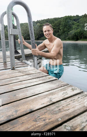 Portrait of a mature man climbing ladder of lake, Baden-Wurttemberg, Bavaria, Germany - Stock Photo