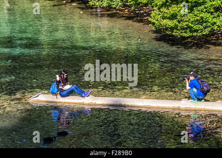 Two young tourists take photographs of clear water of Alpsee lake - Hohenschwangaü Village, Schwangau, Bavaria, - Stock Photo
