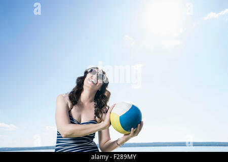 Mature woman playing volleyball on the beach, Bavaria, Germany - Stock Photo