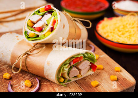 Healthy chicken wraps on a rustic chopping board. - Stock Photo