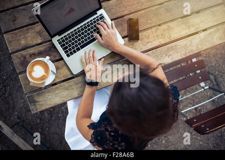 Top view of female using her laptop at a cafe. Overhead shot of young woman sitting at a table with a cup of coffee - Stock Photo