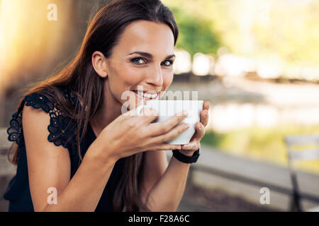 Beautiful young woman holding a cup of coffee looking at camera smiling. Cheerful female enjoying a cup coffee at - Stock Photo