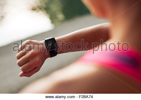 Close up image of young woman checking the time on smartwatch device after jog, outdoors. - Stock Photo