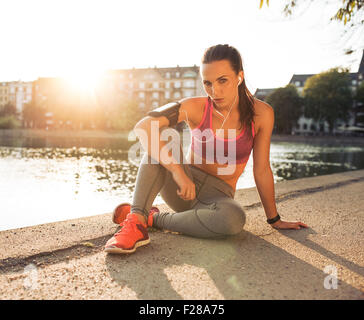 Portrait of fit young woman sitting on the street along a pond. Fitness female taking break from outdoor running - Stock Photo