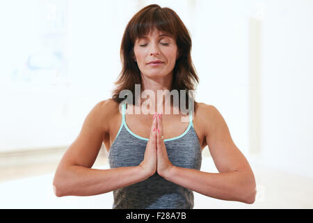 Portrait of a beautiful mature woman sitting in Anjali Mudra yoga pose at the gym meditating. Female fitness trainer - Stock Photo