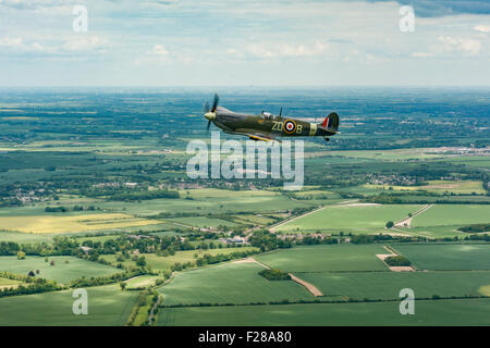Supermarine Spitfire Mark IX MH434 originally of 222 Squadron Royal Air Force, flying over the Cambridgeshire countryside. - Stock Photo