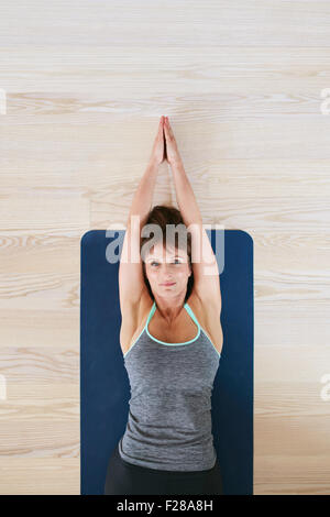 Top view of woman lying on floor doing stretching exercise. Fitness woman exercising on yoga mat. - Stock Photo