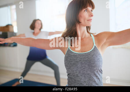 Fitness trainer doing the warrior pose during yoga class. Yoga teacher performing Virabhadrasana position in gym - Stock Photo
