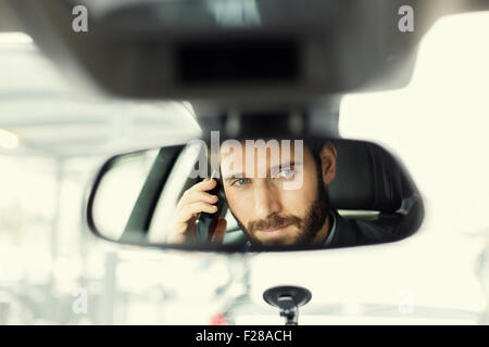 Cheerful man on mobile phone in the car. Reflection in the mirror - Stock Photo