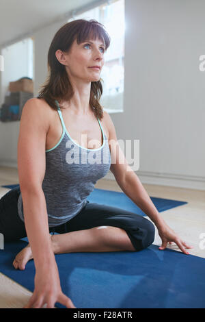 Portrait of fit woman doing chest opener yoga pose at gym with her one leg bend and another stretched on exercise - Stock Photo