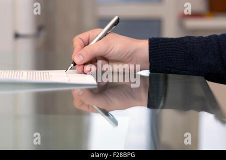 Hands of man signing formal paper - Stock Photo