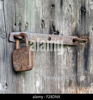 Old wooden doors locked with rusty padlock - Stock Photo