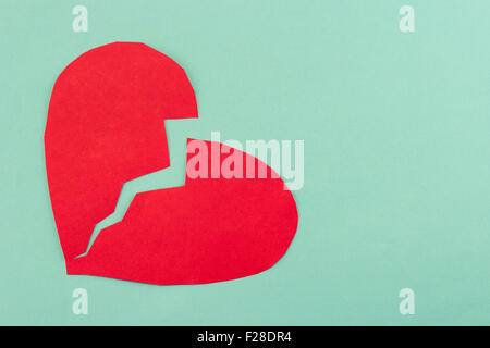 close up of paper broken heart on blue background - Stock Photo
