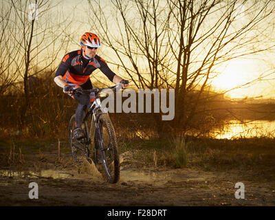 Mature man riding mountain bike on dirt track, Bavaria, Germany - Stock Photo