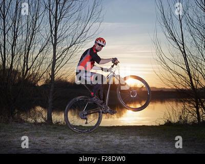 Mature man doing stunts on mountain bike during sunset, Bavaria, Germany - Stock Photo