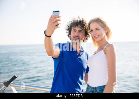 Portrait of a happy couple making selfie photo on smartphone outdoors - Stock Photo