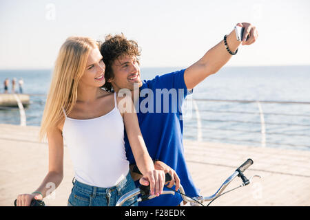 Portrait of a smiling man and woman making selfie photo on smartphone outdoors - Stock Photo