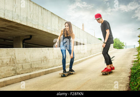 Skateboarder woman and man rolling down the slope - Stock Photo