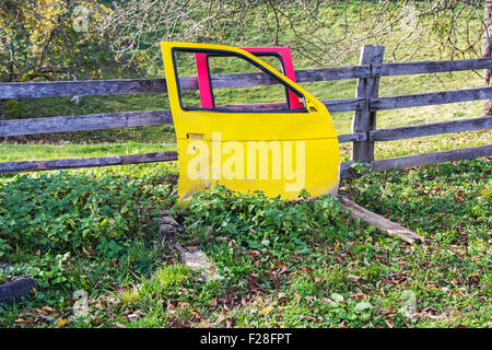 Yellow and red Car doors wreck in the meadow - Stock Photo