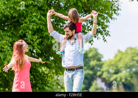 Family walk - Father carrying kid on his shoulder on a walk in summer - Stock Photo
