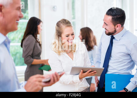 Business people in office working as team, woman showing man presentation on tablet computer - Stock Photo