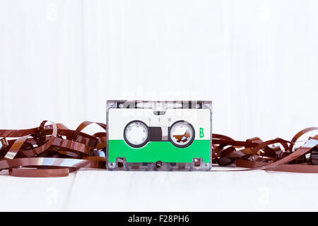 Audio cassette with subtracted out tape on wooden background - Stock Photo