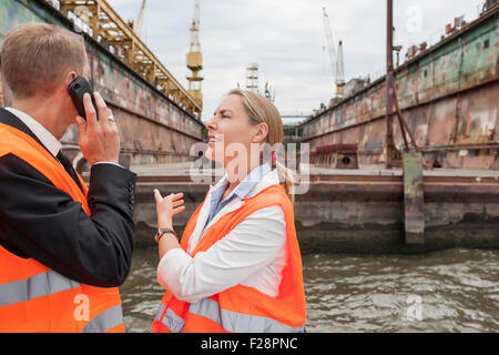 Two business people discussing at harbour, Hamburg, Germany - Stock Photo