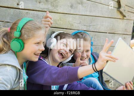 Three friends sitting in playground and listening music, Munich, Bavaria, Germany - Stock Photo