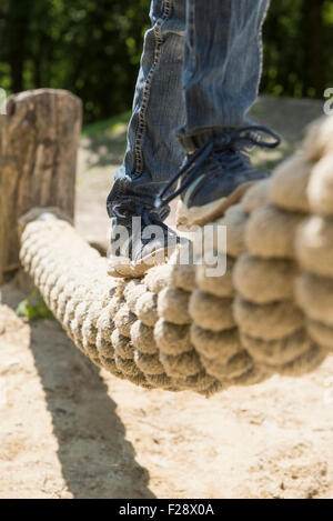 Girl balancing on rope in playground, Munich, Bavaria, Germany - Stock Photo