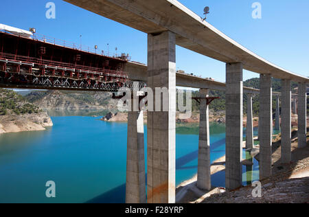 Railway bridge under construction in parallel with highway bridge on landscape blue sky and lake - Stock Photo