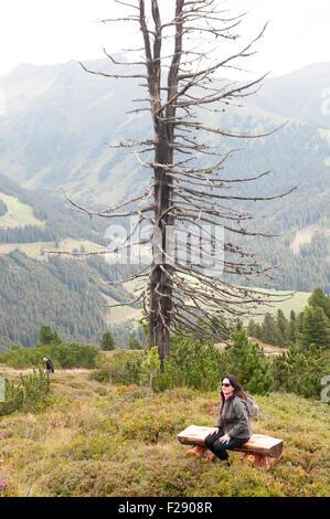Isskogel mountain peak near Gerlos, Tyrol, Austria female hiker rests on a bench - Stock Photo
