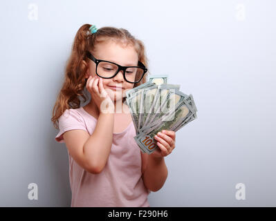 Dreaming cute kid girl looking on money and thinking how can spend its - Stock Photo