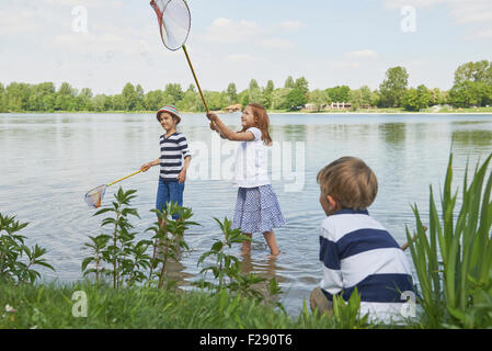 Three friends fishing in the lake, Bavaria, Germany - Stock Photo