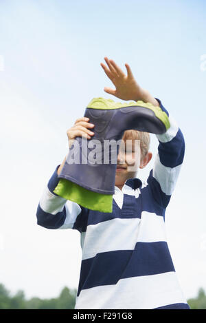 Boy pouring water out of a rubber boot, Bavaria, Germany - Stock Photo