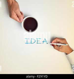 high-angle shot of a young man with a cup of coffee and a young woman writing the word idea with a pen - Stock Photo