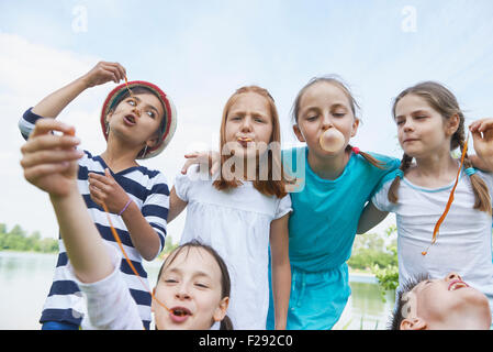 Group of friends playing with bubble gums, Bavaria, Germany - Stock Photo