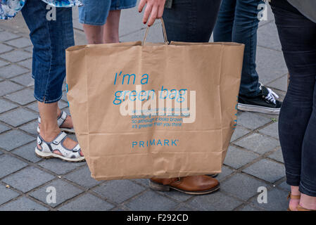 A customer holding a Primark 'green' brown paper bag made from recycled cardboard and paper bags. - Stock Photo