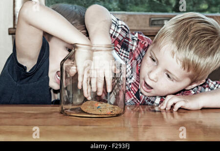Two boys compete and reach for last cookie - Stock Photo