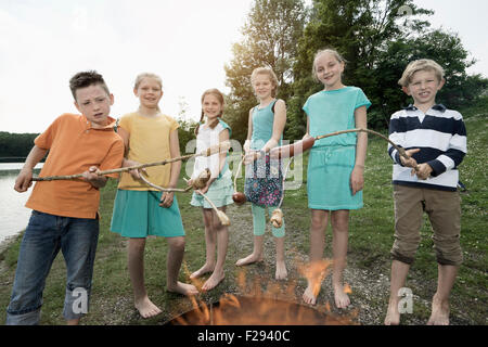 Group of friends preparing sausages on campfire, Bavaria, Germany - Stock Photo
