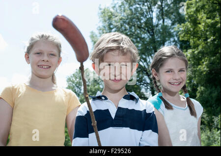 Three friends preparing sausage on campfire, Bavaria, Germany - Stock Photo