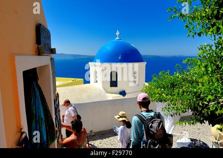 Tourists walking by a typical blue dome church on the island of Santorini Greece - Stock Photo